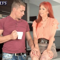 Busty over 6o redhead Charlotta models sexy legs in skirt before giving handjob
