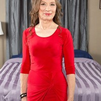 Over 60 model Mona posing fully clothed in red dress and pantyhose