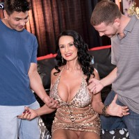 Busty older babe Rita Daniels exposes large tits for 2 young studs to suck on