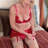 Blonde granny Scarlet Andrews jerking cock and giving titjob in red lingerie