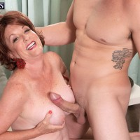 Busty redhead MILF over 60 Gabriella LaMay jerking big cock and receiving oral sex
