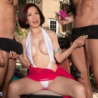 Mature Asian pornstar Kim Anh jerks off two studs beside swimming pool
