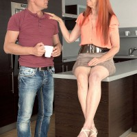 Redheaded 60 MILF Charlotta giving a fully clothed handjob in kitchen