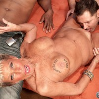 Busty and tattooed over 70 MILF pornstar Sandra Ann jerking off two cocks at once