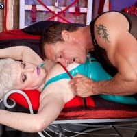 Latex and black stocking attired granny undergoing BDSM torture from man with crop