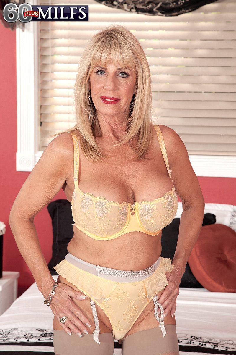 Stocking and garter adorned blonde MILF over 60 Phoenix Skye baring large tits