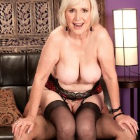 Lingerie and stockings attired MILF over 60 Lola Lee baring big tits before giving BJ
