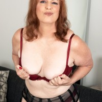 Redhead MILF over 50 Brie Daniels uncovers her natural tits and full bush