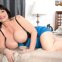 Dark haired mature MILF Elektra sets her giant tits free of a short dress on a bed