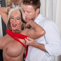 Hot cougar Sally D'Angelo has her knockers freed from a red dress by her toy boy