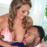 Busty 50 plus MILF Torri Lee bares her tits while seducing a younger black man