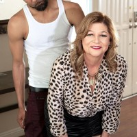 Sexy 60 MILF Brenda Douglas seduces a younger black man in a black miniskirt