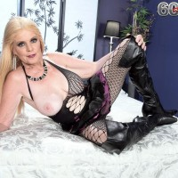 Blonde 60 plus MILF Charlie lets one of her boobs loose of see thru attire on bed