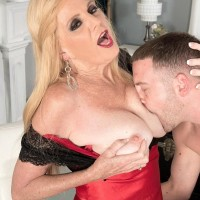 Over 60 blonde Charlie seduces her toy boy on a bed in lingerie and black hosiery
