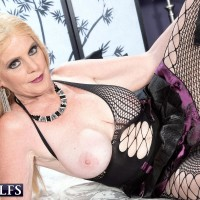 Blonde 60 plus model Charlie exposes big tits in leather boots and mesh hosiery