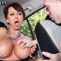Big titted 60 plus MILF Gina Milano seduces a younger boy inside a vehicle