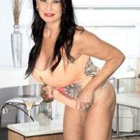 Sexy 60 plus woman Rita Daniels frees her large tits from dress in sheer panties