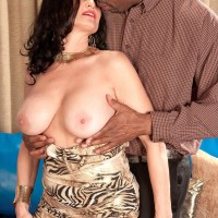 Aged dark-haired X-rated starlet Rita Daniels revealing huge tits before bi-racial sex