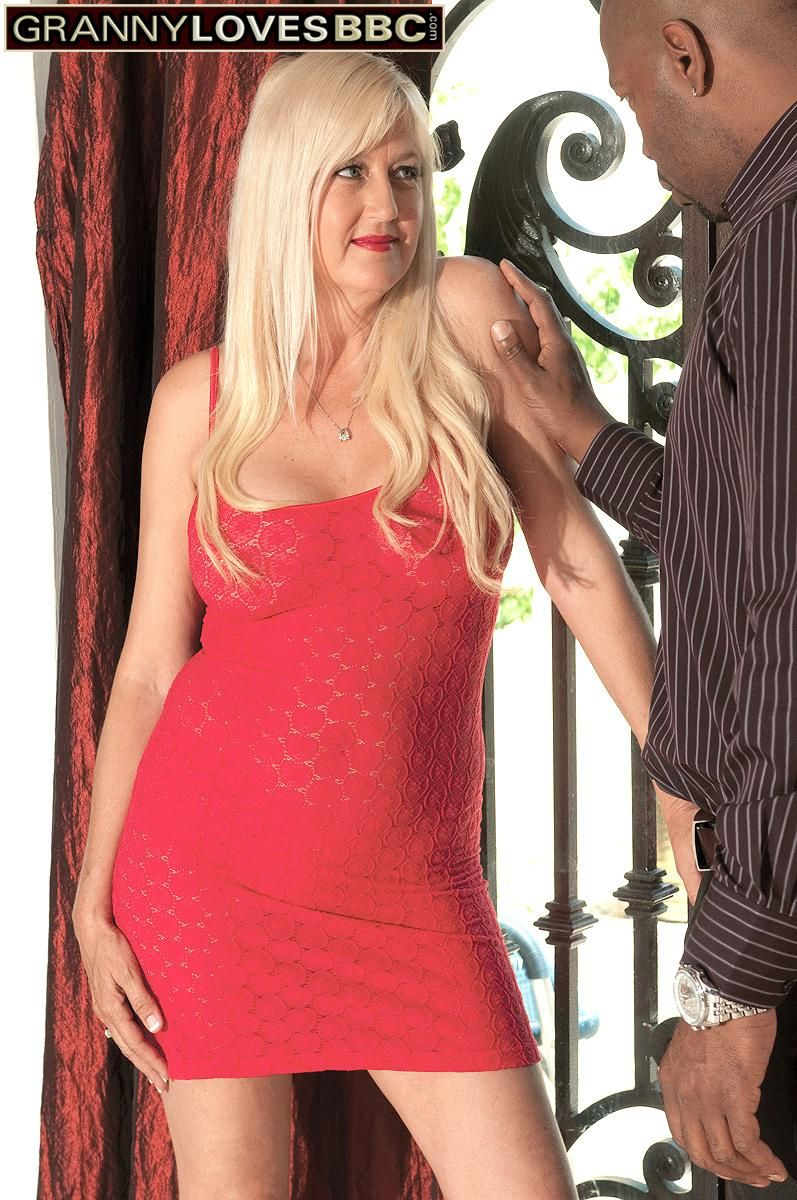 Fair-haired grannie Marina Johnson greets her ebony lover in crimson sundress and matching high-heeled shoes