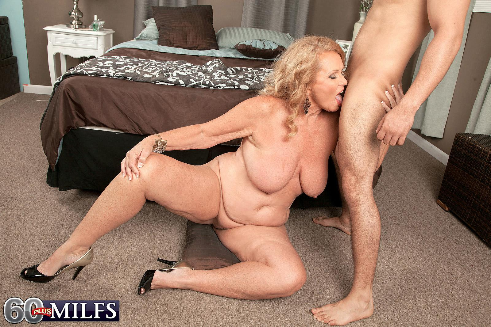 Bosomy blond grandmother giving blowjob on knees before XXX doggie-style sex