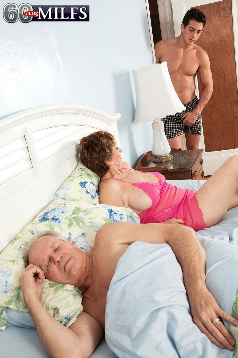 Bosomy redhead granny Bea Cummins stroking off enormous penis while cuckold hubby sleeps