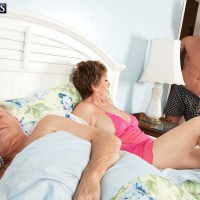 Bosomy redhead granny Bea Cummins stroking off enormous penis while cuckold hubby sleeps