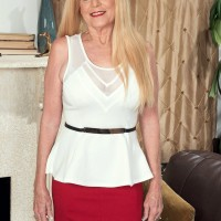 Mature blonde lady has her big natural tits unleashed by younger man in red skirt