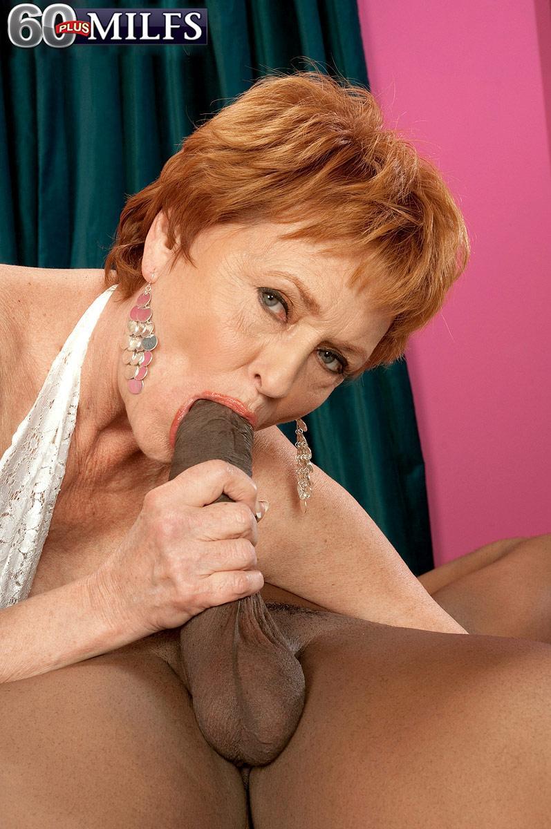 Crimson hair grandma XXX film starlet Valerie blowing a huge black rod in white lingerie