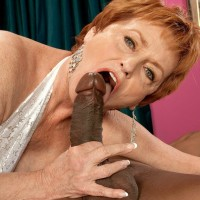 Crimson hair grandma XXX film starlet Valerie blowing a huge black rod in white lingerie