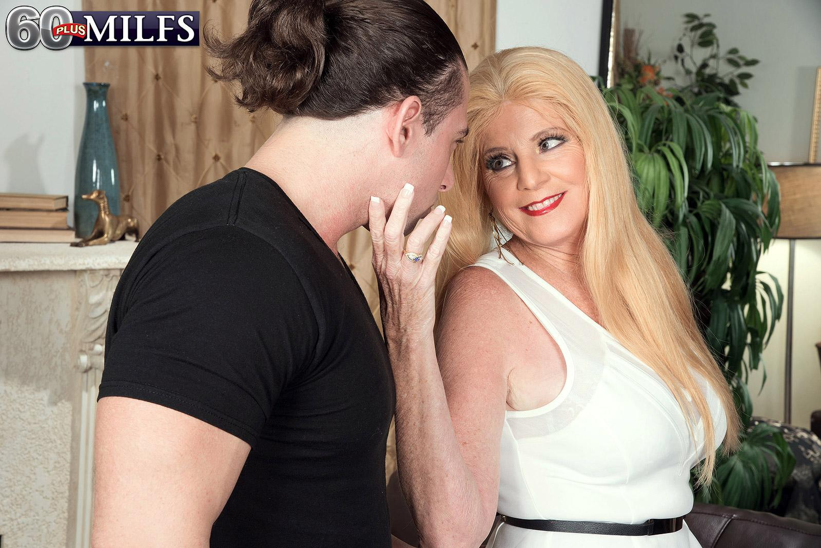 Elder blonde lady Charlie has her big hooters uncovered by junior man in a red skirt