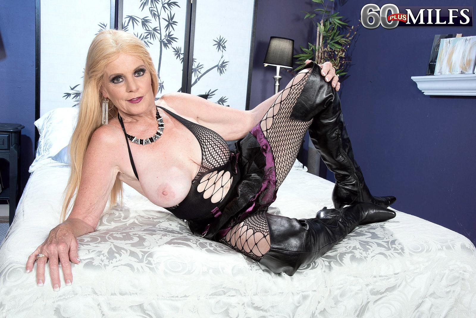Golden-haired grannie Charlie unleashes her hefty boobies in over the knee boots and fishnet body-suit