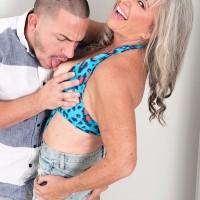 Gorgeous 60 plus MILF Silva Foxx seduces a junior man by showcasing her breasts in a denim miniskirt