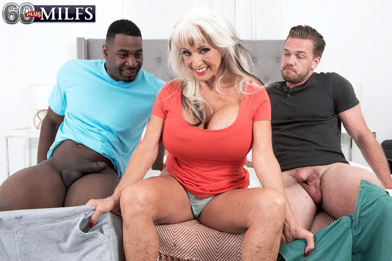 Killer 60 plus MILF Sally D'Angelo sucks on a big black dick and a immense white dick simultaneously