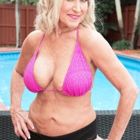 60 plus lady has her big natural boobs lubed up by the much younger pool boy