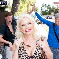 Light-haired granny Cammille Austin seduces two young dudes in a short dress