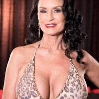 Older dark-haired X-rated film star Rita Daniels flashing no panty upskirt during melon sucking