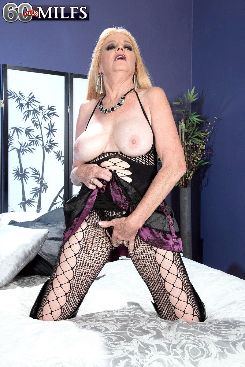 Over 60 ash-blonde MILF baring hefty natural boobs in torn hosiery and lengthy boots