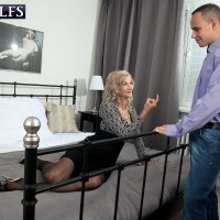 Over 60 MILF Beata wraps her red lips around a younger man's penis on a bed