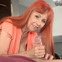 Redheaded grandmother with great gams and hefty all-natural boobs giving hand job in kitchen