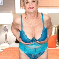 Short haired 60 plus MILF Lin Boyde baring monster-sized tits from lingerie in stockings