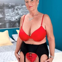 Short haired grannie Joanne Price seducing younger boy in tights and garter