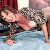 Solo granny Sydni Lane taunting on bed by showing off melon-holder in tights