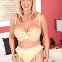 Mature golden-haired adult film star Bethany James draining two peckers in lingerie and tights